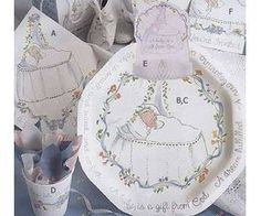 Paper products and decorations designed for a christening enhance the party theme.