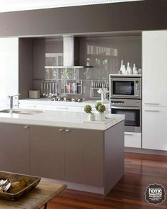 Kitchen: Modern design: glass backsplash with taupe or champagne coloured cabinets.