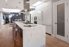 Modern white kitchen with calacatta marble island and miele built in appliances