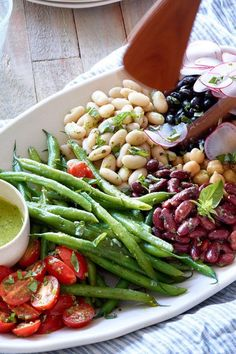 Channel your inner food stylist while arranging the beans and vegetables for this show-stopping composed bean salad recipe. Serve at a potluck or for a beautiful salad at brunch alongside grilled chicken, scallops or fish. #gameday #football #healthygamedayrecipes #superbowlfood #superbowlrecipes #healthyappetizers #heathytailgaiting #tailgaitingfood #tailgatefood #recipe #eatingwell #healthy