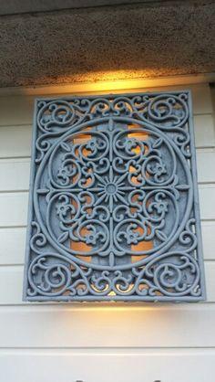 Buitenlamp gemaakt van een rubberen deurmat gelijmd op een houten frame over een lamp gehangen.