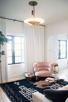 pink accent chair, black and white moroccan rug, white curtains, mid century light fixture, lots of natural light and high ceilings