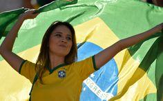 12/6 - Torcedora segura a bandeira do Brasil em dia de estreia da seleção