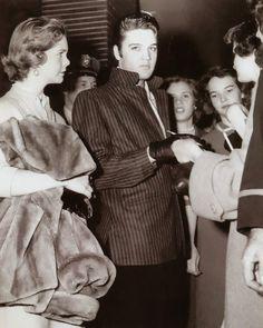 Elvis Presley signing autographs for fans.