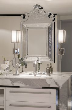 Elegant bathroom features a mirrored accent wall adorned with a Venetian mirror flanked by contemporary nickel wall sconces over an undermount sink and modern faucet framed by a marble waterfall edge counter with white lacquered drawers below adorned with oversize nickel pulls.