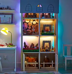 A bookshelf used as a toy house and filled with toys. LED strip lights light up each compartment and there is blind hanging over the front at the top with windows cut into it.