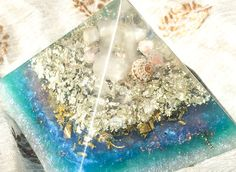 An orgonite pyramid with White Gold to channel the balanced energy of the Sun and Moon. A Madagascar Quartz point floats at the tip of this orgone crystal pyramid within a crystal grid of sunstone and moonstone, and a shell from the Atlantic Ocean. A bed of rose quartz rests over dense layers of white gold, sterling silver, pyrite, brass and copper. The Sun and Moon orgonite pyramid is a powerful Feng Shui tool offering true balance to you and your environment. As the orgonite matrix…