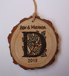 """Handmade Monogram Couples Christmas Ornament Rustic Engraved Wood tree Slice. Beautifully rustic, eco-friendly tree slice Christmas or holiday ornament, engraved by hand with your first names, initial, and date. Each monogrammed tree slice measures approx 3"""" to 4"""" in diameter, as they are an all natural product, there will be variances. The oak leaves in the background of the initial are hand painted with a light wash of green, letting the natural grain of the wood come through. These…"""