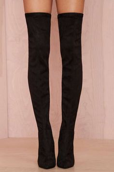 These black suede thigh high boots have a suede upper, pointed toe, and zip closure at side.