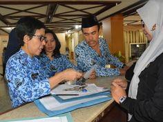 Petugas mengumpulkan kartu tanda pengenal pegawai yang terjaring sidak