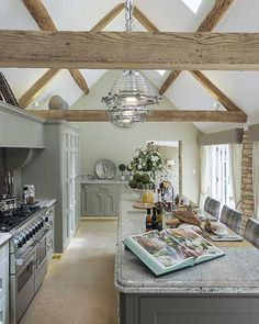 With vaulted ceilings and bathed in natural light, this beautiful kitchen by Rixon Architects features handmade units in subtle green and grey tones with contrasting granite and wood worktops with Castile limestone flagstone floor tiles in 60cm width and random widths. #FlagstoneFlooring #LimestoneFlagstones #CotswoldFlagstones