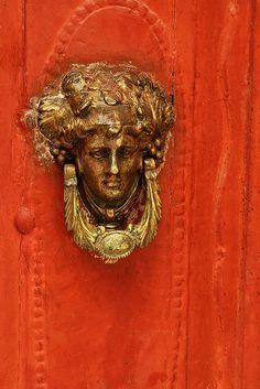 Doorknocker, Symi island    Red wooden wall and golden door knob