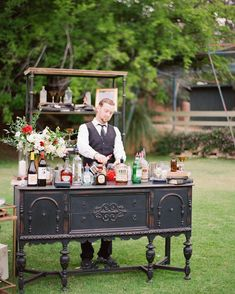 "Vintage home furnishings were transformed into a chic drink station at this whimsical wedding. The dresser and shelving unit held books, knick-knacks, and flowers, plus all the ingredients necessary for a makeshift cocktail bar. The final touch? A tongue-in-cheek sign stating ""Prohibition Ends Here."""