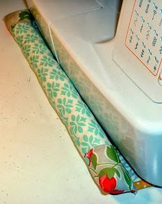 A long pincushion attached to a quilted mat that goes under the sewing machine. Quiets the noise and shaking, and gives you a handy place for pins.