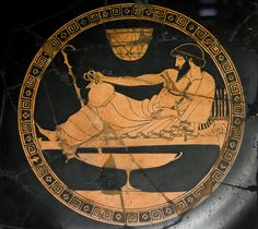 """A barbed man is reclining on a """"kline"""". He holds in the right hand an """"oinochoe"""". A basket is suspended to the ceiling. A large cup stays in front of him.   Attic red-figured kylix Made in Athens by the Douris Painter 500 – 450 BC From Chiusi, Siena Florence, Museo Archeologico Etrusco"""