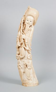 Japanese carved ivory fisherman group - large tusk section with carved figure of elderly fisherman and two children, 24 in. H.