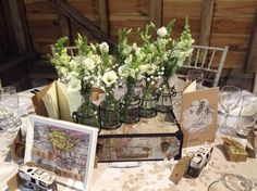 Table Centre - Bottles on a suitcase containing all white Lisianthus, Antirrhinums, Gyp and Foliage #TableCentre #WeddingFlowers #White