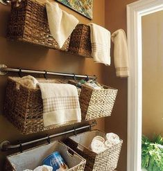 Hang baskets on curtain rods to take advantage of unused wall space. The baskets can be attached with zip ties or S-hooks (I think that's the proper name for them). This is a perfect idea for storing extra hand towels in the bathroom, organizing kids' toys, keeping craft items together, or even storing items in the garage. #diyorganizingideas