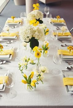 Yellow tulips, ranunculus, freesia, and white hydrangea in large bases and bud vases atop a crinkle ivory linen and yellow napkins