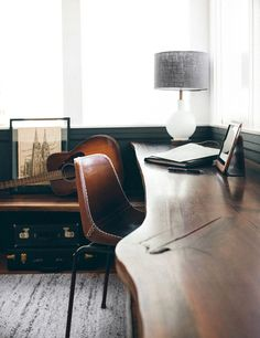 reclaimed wood desk attached to the wal. guitar. leather desk chair reminds me of a cathcher's glove. black painted woodwork and architecture drawing. clean and simple