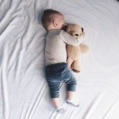 Baby sleeping while hugging his little bear