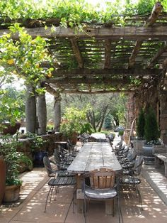 a wonderful rustic table and vintage chairs set under an arbor - so welcoming