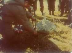 Argentine soldiers burying a british soldier with their flag.   Falklands War, 1982.