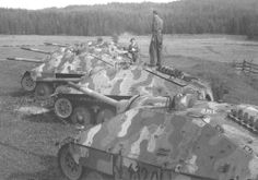 Multiple captured Hetzers lined up outside a forested area by British forces.
