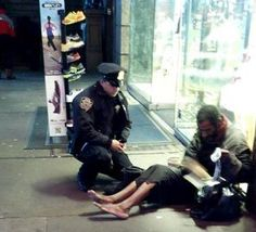 This photo provided by Jennifer Foster shows New York City Police Officer Larry DePrimo presenting a barefoot homeless man in New York's Time Square with boots. Foster was visiting New York with her boyfriend on Nov. 14, when she came across the shoeless man asking for change in Times Square. As she was about to approach him, she said the officer  came up to the man with a pair of all-weather boots and thermal socks on the frigid night. She took the picture on her cellphone.