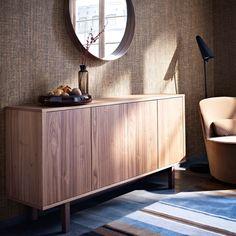 """Ein Wohnzimmer mit STOCKHOLM Sideboard aus Nussbaumfurnier mit STOCKHOLM Servierschale in Braun, darüber STOCKHOLM Spiegel aus Nussbaumfurnier und daneben STOCKHOLM Drehsessel mit Bezug """"Sandbacka"""" in Dunkelbeige"""