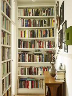 library in the hallway clever use of space shelves vary in depth to hold paperbacks vs. hard backs/larger book Brixton house in The Guardian
