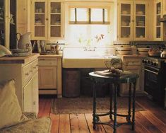 apron sink. plank floors. butcher block countertop. table for island. chicken wire in cabinetry. storage under sink-love it