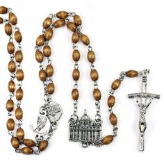 #Rosary with natural #wooden #beads and oxidized  Papal #Crucifix. This #Rosary also features an oxidized centerpiece of the St. Peter Basilica with embossed images of St. Peter and St. Paul on the reverse side. The our father beads consist of medals with embossed images of the four Basilicas, St John Lateran, St Peter, St Paul, and St Mary Major, with images of the Saints on the reverse side. This #Rosary comes in a clear box with an image of St. Peter Basilica.
