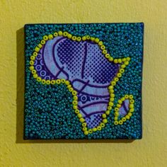Shop: Canvas D'Afrique - Blue Shades. This Africa is partially beaded on canvas in green and yellow with a center of varying blue patterned fabrics. Size: 10cm x 10cm. By Beadoir D'Afrique