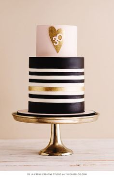 A pink and gold cake table featuring black and white stripes, gold glittering hearts and sparkling details. Perfect for a 30th birthday party.