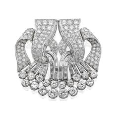 A diamond double-clip brooch, French, circa 1950  Each opposing openwork clip formed of scrolled ribbons set throughout with single, baguette and old round brilliant-cut diamonds, length of each clip 42mm, French control marks for 18ct gold and platinum, the diamonds estimated to weigh approximately 7.80cts in total