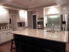 Gone are the cherry wood cabinets and in are the refinished antique white glazed cabinets. This kitchen looks fresh, clean and ready for entertaining!