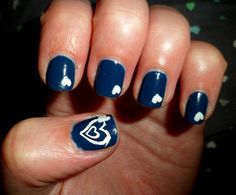 navy blue nails with white hearts and white heart on thumb
