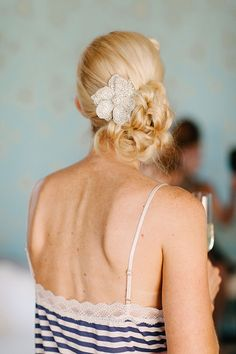 A curly low chignon with a floral headpiece | Brides.com