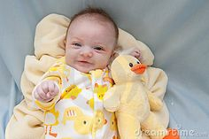 Newborn baby girl around two to three months in age laying on a yellow fleece blanket wearing a onesie sleeper or sleep 'n play outfit with ducks and holding a stuffed duck toy. Background is light blue fabric.