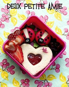 Cute! - Babybel cheese with olives, candy eyes, & chocolate chips for ladybugs; jelly sandwich with cookie cutter heart cutouts; sliced strawberries; and dried cranberries.