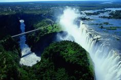 The Victoria Falls is a beautiful waterfall that is on the border of Zambia and Zimbabwe in Africa. The waterfall is 355 feet. There is even something called the Devil's Pool that allows you to play on the edge of Victoria Falls. World's Most Beautiful, Beautiful Places To Visit, Cool Places To Visit, Places To Travel, Chutes Victoria, 7 Natural Wonders, Paraiso Natural, Largest Waterfall, Les Cascades