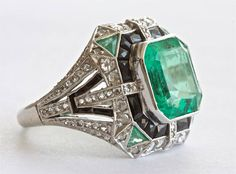 Columbian Six Carat Emerald Platinum Ring. This magnificent ring features a 6.11 carat Columbian Emerald that has been certified by AGL. The ring contains emerald accents, onyx and diamonds.