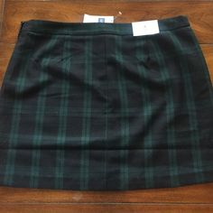 """NWT GAP ADORABLE PLAID MINI SKIRT. 8 NWT this GAP skirt is so cute in a green and black plaid. Mini skirt is 15 1/2"""" in length and 17"""" across waist. Made of polyester and rayon. Won't be bad to wrinkle. Fabric is not heavy weight so it can be worn year round. fully lined. Side zip closure. Size 8 GAP Skirts Mini"""