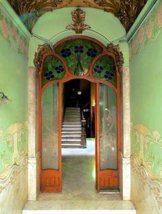 Art Nouveau Entrance hall from late 1800s depicting a green floral decorative design both on walls and ceiling. Bold stain glass also featuring a floral theme sits arched over the doorway reflecting hanging vines. The timber work framing the doorway representing the trunks of the vines leading to the foliage above. All imagery reflecting on nature which was a common style element of the time.