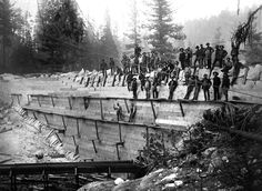 Workmen pose for a photograph in the summer of 1892 on the wood face of the rock-filled Shaver sawmill dam.