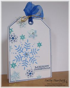 handmade Christmas card ... tag shape ... white with stamped snowflakes in blues ... blue rhinestones ...  organza ribbon tied with gold cord ... beautiful!!