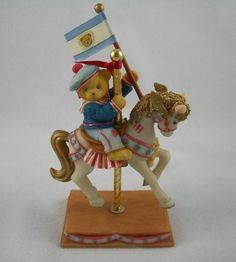 """One of a set of carousel figurines this one depicts a boy on a horse carrying a flag. It is subtitled """"Friends Like You Are Always True Blue"""" Th"""