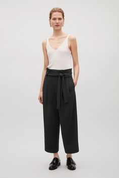 Designed with a pleated waist and wide tunnel belt loops, these trousers are made from a loose, fluid fabric. A wide leg style that are dropped at the crotch, they are completed with in-seam pockets and a detachable tie.