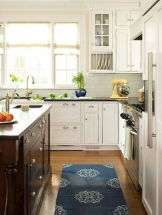This kitchen has all the hallmarks of vintage cottage style: bin-style pulls, exposed hinges, inset flat-panel cabinet doors and drawers, open plate racks, and glass doors in some of the upper cabinets. The comfortable familiarity of the cottage look cleverly disguises modern amenities and functions: Custom drawers hold double dishwasher drawers to the right of the sink, vertical storage keeps trays and baking sheets in order, and extra-deep drawers stash cereals and snacks. An island made out